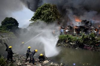 Firefighters extinguish flames as a fire engulfs an informal settlers area beside a river in Manila on August 11, 2017. Fires are common hazards in the sprawling capital, where millions live in hovels made of scrap wood and cardboard and fire safety regulations are rarely imposed. / AFP PHOTO / NOEL CELIS