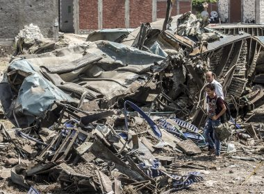 An Egyptian man and a boy look at the wreckage from the prior day of a fatal rail collision in the area of Khorshid on the outskirts of Egypt's Mediterranean city of Alexandria from the day before, on August 12, 2017. The toll from the accident on August 11, 2017, when two trains hurtled into each other near Egypt's second-largest city, has risen to 40 dead and 123 wounded, said health ministry spokesman Khaled Moujahed, as local media said the number of fatalities was likely to rise. / AFP PHOTO / KHALED DESOUKI