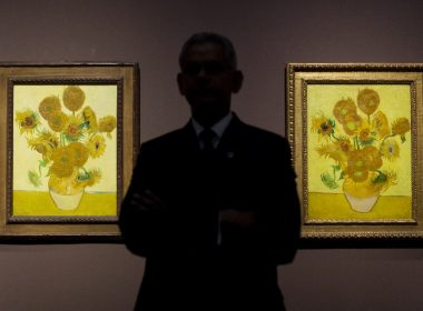 """(FILES) This file photo taken on January 24, 2014 shows a gallery supervisor posing for photographs with two versions of Dutch artist Vincent van Gogh's Sunflowers paintings at the National Gallery in London. Five versions of Vincent van Gogh's masterpiece painting """"Sunflowers"""" will be united across three continents for the first time on August 14, 2017 via a consecutive livestream feed, the Van Gogh museum in Amsterdam has said. / AFP PHOTO / LEON NEAL"""