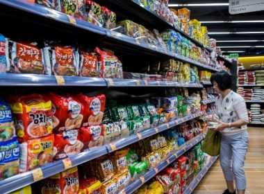 This picture taken on August 17, 2017 shows a customer walking past different brands of instant noodles for sale in a supermarket in Hong Kong.  From decades-old holes in the wall to multi-million dollar businesses, Hong Kong's noodle scene is a sprawling moneyspinner in a city that runs on quick and affordable comfort food. / AFP PHOTO / Isaac LAWRENCE / TO GO WITH HongKong-lifestyle-food-noodles-business, FEATURE by Elaine YU