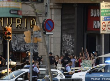 """People leave a fastfood with hands up as asked by policemen after a van ploughed into the crowd, killing two persons and injuring several others on the Rambla in Barcelona on August 17, 2017. A driver deliberately rammed a van into a crowd on Barcelona's most popular street on August 17, 2017 killing at least two people before fleeing to a nearby bar, police said.  Officers in Spain's second-largest city said the ramming on Las Ramblas was a """"terrorist attack"""" and a police source said one suspect had left the scene and was """"holed up in a bar"""". The police source said they were hunting for a total of two suspects. / AFP PHOTO / Josep LAGO"""