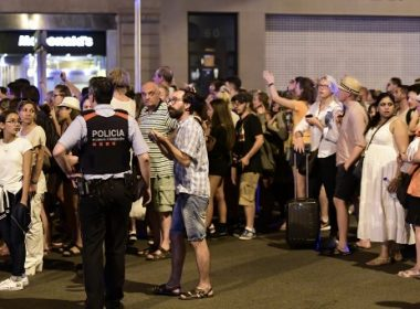 "Tourists wait for the police to allow them to come back to their hotel on the Rambla boulevard after a van ploughed into the crowd, killing at least 13 people and injuring around 100 others on the Rambla in Barcelona, on August 18, 2017. A driver deliberately rammed a van into a crowd on Barcelona's most popular street on August 17, 2017 killing at least 13 people before fleeing to a nearby bar, police said.  Officers in Spain's second-largest city said the ramming on Las Ramblas was a ""terrorist attack"". The driver of a van that mowed into a packed street in Barcelona is still on the run, Spanish police said. / AFP PHOTO / JAVIER SORIANO"