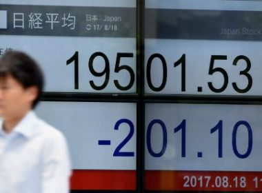 A man walks past a stock quotation board flashing the Nikkei 225 key index of the Tokyo Stock Exchange in front of a securities company in Tokyo on August 18, 2017.  Tokyo stocks opened lower, following sharp falls in New York on a deadly attack in Spain and rising concerns over the fate of US President Donald Trump's economic agenda. / AFP PHOTO / Toru YAMANAKA
