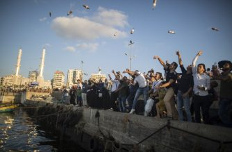 Palestinian activists throw bottles into the sea containing messages against the siege of the Gaza Strip at the port in Gaza City on August 22, 2017. The initiative came after a message in a bottle cast into the sea by a holidaying British couple on the island of Rhodes was found by a Palestinian fisherman after it washed up on the Gaza Strip. / AFP PHOTO / MAHMUD HAMS