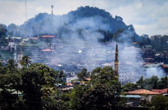 Smoke rises from houses as battles continue in Marawi on the southern island of Mindanao on August 28, 2017. Soldiers killed 10 suspected militants on August 28 as they attempted to infiltrate by boat, a Philippine city that has been under siege by pro-Islamic State gunmen for over three months, officials said. / AFP PHOTO / Ferdinand CABRERA