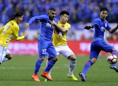 Shanghai Shenhua's Argentine striker Carlos Tevez (2L) fights for the ball with Yang Xiaotian (2R) of Jiangsu Suning during their Chinese Super League football match in Shanghai on March 5, 2017. / AFP PHOTO / STR / CHINA OUT