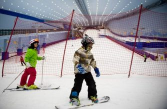 In this picture taken on August 22, 2017, children snowboard and surf at the Wanda Harbin Ice and Snow Park in Harbin. At Dalian Wanda Group's new Ice and Snow Park, chilly winds blew snowflakes around skiers zipping down the manmade slopes of the world's largest indoor ski park, a potent symbol of China's ambitions to turn itself into a winter sports powerhouse ahead of the 2022 Winter Olympics in Beijing. / AFP PHOTO / Nicolas ASFOURI / TO GO WITH China-lifestyle-ski, FEATURE by Yanan WANG