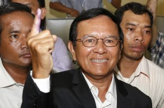 """(FILES) This file photo taken on June 4, 2017 shows Kem Sokha (C), leader of the Cambodia National Rescue Party (CNRP), showing his ink-covered finger after voting at a polling station in Phnom Penh. A Cambodian court on September 5, 2017 charged opposition leader Kem Sokha with treason and espionage over an alleged conspiracy with unnamed """"foreigners"""" -- a charge that carries up to 30 years in jail.  / AFP PHOTO / STR"""