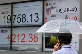 A man walks in front of a stock quotation board flashing the Nikkei 225 key index of the Tokyo Stock Exchange (L) and the exchange rate for the yen against the US dollar (R) in Tokyo on September 12, 2017. Tokyo stocks opened higher September 12 following a market rally on Wall Street on receding worries about North Korea and Hurricane Irma. / AFP PHOTO / Kazuhiro NOGI
