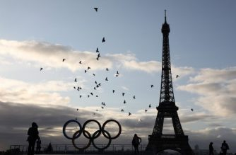 Pigeons fly past the Olympic rings installed on the Esplanade du Trocadero near the Eiffel tower following the Paris' nomination as host for the 2024 Olympics, are pictured on September 14, 2017 in Paris.  / AFP PHOTO / LUDOVIC MARIN