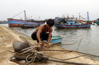 A fisherman anchors his fishing boat  at a port  in the central province of Quang Tri on September 14, 2017, as typhoon Doksuri approaches the country's central coast./ AFP / Vietnam News Agency /