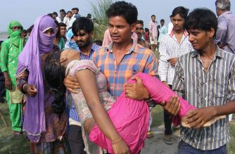 An Indian man carries the body of a woman after a boat capsized on the Yamuna river near the city of Baghpat in the northern state of Uttar Pradesh on September 14, 2017. At least 20 people died when the boat packed with laborers capsized on the Yamuna river in northern India, an official said. / AFP /