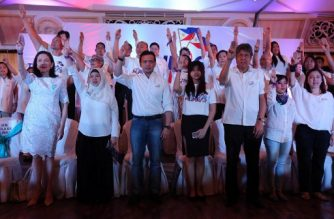 "This photo taken on September 19, 2017 shows Philippine Senators Risa Hontiveros (L), Antonio Trillanes (3rd L), Francis Pangilinan (3rd R) and others raising a three-finger salute, as they launched the Tindig Pilipinas (Arise Philippines) movement in Manila. Critics of Philippine President Rodrigo Duterte have adopted the three-finger salute from the hit ""Hunger Games"" films as a sign of resistance against his rule and drug war killings. The sign is in contrast to Duterte's own iconic gesture, a clenched fist raised at or above eye level that is immensely popular with his support but which opponents have likened to Nazi leader Adolf Hitler's hand salute. / AFP PHOTO / STR"
