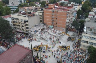 This aerial view shows rescuers, firefighters, policemen, soldiers and volunteers searching for survivors in a flattened building in Mexico City on September 20, 2017 a day after a strong quake hit central Mexico. A powerful 7.1 earthquake shook Mexico City on Tuesday, causing panic among the megalopolis' 20 million inhabitants on the 32nd anniversary of a devastating 1985 quake. / AFP PHOTO /