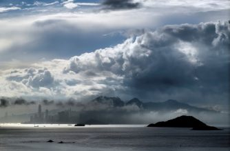 A general view shows clouds above Hong Kong island early on September 22, 2017. Standard & Poor's on September 22, slashed Hong Kong's top-notch credit rating, a day after lowering China's, warning of potential spillover risks the mainland's ballooning debt pile. / AFP PHOTO / Anthony WALLACE
