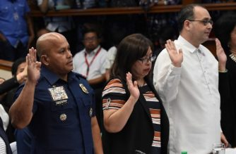 (FILES) This file photo taken on August 22, 2016 shows Philippine National Police (PNP) Director General Roland dela Rosa (L) and Commission on Human Rights Commissioner Chito Gascon (R) taking their oaths at the start of a senate inquiry into a spate of extrajudicial killings in Manila. / AFP PHOTO / TED ALJIBE