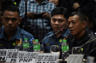 """(L-R) Jeremias Pereda, Jerwin Cruz, and Arnel Oares, accused policemen of allegedly killing 17-year-old student Kian Delos Santos during an anti-drug raid, attend a Senate hearing in Manila on August 24, 2017.  Philippines' President Rodrigo Duterte launched an unprecedented crackdown on illegal narcotics after winning the presidency last year on a promise to kill tens of thousands of criminals. The numbers saw a sudden increase weeks ago, with Duterte praising officers who shot dead 32 people in a single province as he urged for more. Following Duterte's call, at least 44 people were killed in various cities, including a 17-year-old boy whose death on August 16 sparked a national furore.people were killed in various cities, including a 17-year-old boy whose death on August 16 sparked a national furore. / AFP PHOTO / TED ALJIBE / """"The erroneous mention[s] appearing in the metadata of this photo by TED ALJIBE has been modified in AFP systems in the following manner: [Jeremias] instead of [Jeremmas]. Please immediately remove the erroneous mention[s] from all your online services and delete it (them) from your servers. If you have been authorized by AFP to distribute it (them) to third parties, please ensure that the same actions are carried out by them. Failure to promptly comply with these instructions will entail liability on your part for any continued or post notification usage. Therefore we thank you very much for all your attention and prompt action. We are sorry for the inconvenience this notification may cause and remain at your disposal for any further information you may require."""""""
