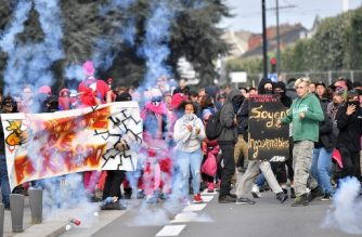 Young protesters back off to avoid tear gas canisters during clashes with anti-riot police within a protest called by several French unions against the labour law reform, on September 12, 2017 in Nantes, western France.  / AFP PHOTO / LOIC VENANCE