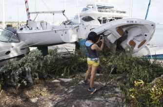 A woman photographs damage and boats brought onto land by Hurricane Irma at a marina in Miami, Florida, September 11, 2017. / AFP PHOTO / SAUL LOEB