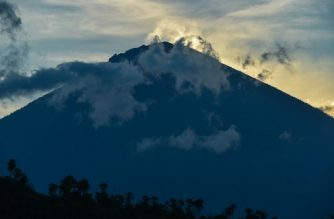 Mount Agung is during sunset in Amed beach, in Karangasem, on Bali island on September 29, 2017. A rumbling volcano on the holiday island of Bali is spewing steam and sulphurous fumes with more intensity, heightening fears of an eruption as officials said the number of evacuees had topped 144,000. / AFP PHOTO / BAY ISMOYO