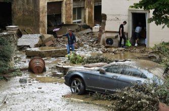 People empty a house in the Livorno area, flooded after heavy rain, on September 10, 2017. At least six people have died in violent rainstorms sweeping across Italy on September 10, 2017, with the Tuscan city of Livorno taking the brunt of the flooding, fire services said.  / AFP PHOTO / STR