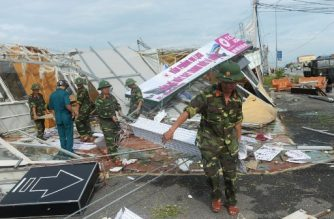Soldiers remove debris in Ky Anh town, in the central province of Ha Tinh, the day after Typhoon Doksuri makes a landfall to the country's central coast on September 16, 2017.  Typhoon doksuri wreaked havoc on central Vietnam lashing the coast with fierce winds and heavy rains as tens of thounsands were evacuated and three people were reported dead in the country's worst storm in years. / AFP PHOTO / HOANG DINH NAM