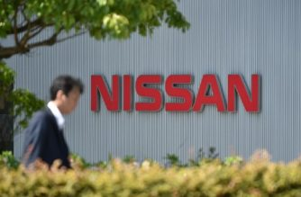 (FILES) This file photo taken on May 11, 2017 shows a man walking in front of the logo of Japan's Nissan Motor Corporation at its global headquarters in Yokohama, Kanagawa prefecture. Nissan said on October 2, 2017 it is recalling some 1.2 million cars in Japan that did not meet domestic rules on final safety inspections. / AFP PHOTO / Kazuhiro NOGI
