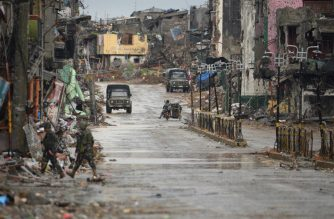 This photo taken on October 17, 2017 shows  soldiers on a street flanked by destroyed buildings in Marawi./AFP / Ted Aljibe/