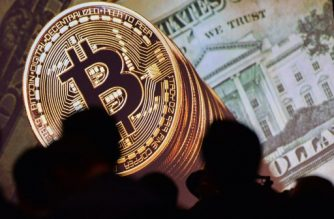 (FILES) This file photo taken on July 04, 2017 shows an image of Bitcoin and US currencies  displayed on a screen as delegates listen to a panel of speakers during the Interpol World Congress in Singapore. Bitcoin surged through the $5,000 level on October 12, 2017 for the first time since the launch of the unregulated virtual currency more than 8 years ago. / AFP PHOTO / ROSLAN RAHMAN