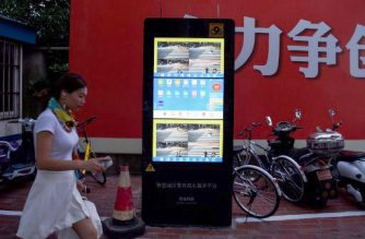 In this photograph taken on August 9, 2017 a Chinese girl walks past the installed facial recognition screen at a road intersection in Shanghai.  From toilet-paper dispensers to fast-food restaurants, travel and crime-fighting, China is taking the lead in rolling out facial-recognition technology. / AFP PHOTO / CHANDAN KHANNA / TO GO WITH STORY:  China-lifestyle-economy-technology-security-facial, FOCUS by Peter STEBBINGS