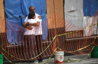 Donny Romero and Jose Luis Tavera embrace each other during the demolition of the building where they used to live, which was seriously damaged by the September 19 earthquake, in Mexico City on October 17, 2017.  An estimated 1,800 buildings in Mexico City suffered serious damage during the 7.1-magnitude quake that hit the country last month, and will have to be repaired or demolished. / AFP PHOTO / PEDRO PARDO