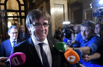 """Catalan regional government president Carles Puigdemont (C) and former Catalan President Artur Mas (L) arrive  at the Catalan regional parliament in Barcelona on October 10, 2017. Catalonia's leader Carles Puigdemont said Tuesday he accepted the """"mandate of the people"""" for the region to become """"an independent republic,"""" but proposed suspending its immediate implementation to allow for dialogue.  / AFP PHOTO / LLUIS GENE"""