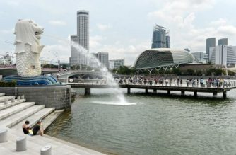 Tourists gather at Merlion park to take pictures overlooking Marina bay in Singapore on August 11, 2016. Singapore on August 11 narrowed its economic growth forecast for this year, citing concerns over the weaker global outlook and the impact of Britain's vote to leave the EU. / AFP PHOTO / ROSLAN RAHMAN