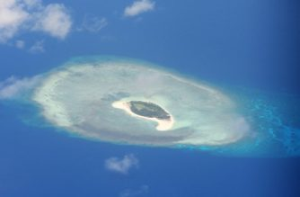 This photo taken on April 21, 2017 shows an aerial shot of a reef in the disputed Spratly islands on April 21, 2017. Philippine Defence Secretary Delfin Lorenzana flew to a disputed South China Sea island on April 21, brushing off a challenge by the Chinese military while asserting Manila's territorial claim to the strategic region. / AFP PHOTO / TED ALJIBE