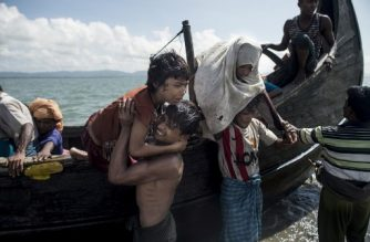 "Bangladeshi men help Rohingya Muslim refugees to disembark from a boat on the Bangladeshi shoreline of the Naf river after crossing the border from Myanmar in Teknaf on September 30, 2017.  More than 2,000 Rohingya have massed along Myanmar's coast this week after trekking from inland villages in Rakhine state to join the refugee exodus to Bangladesh, state media reported September 30. They follow more than half a million fellow Rohingya who have emptied out of northern Rakhine in a single month, fleeing an army crackdown and communal violence the UN says amounts to ""ethnic cleansing"".  / AFP PHOTO / FRED DUFOUR"