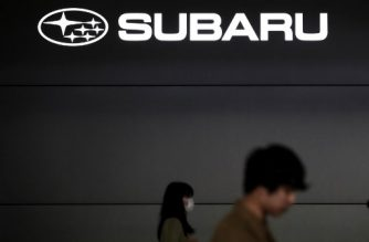 People walk past the logo of Japan's automaker Subaru outside the company's headquarters in Tokyo on October 27, 2017. Subaru said it allowed uncertified staff to do inspections on some vehicles for more than three decades, becoming the latest Japanese firm hit by a quality scandal. / AFP PHOTO / BEHROUZ MEHRI