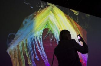 A woman takes a photo of the Kingdom of Colors exhibition, an immersive visual experience from French filmmaker Thomas Blanchard and artist Oilhack, at the ARTECHOUSE gallery in Washington, DC on November 8, 2017. It all began as an accident. After hurting his wrist, artist Oilhack started mixing paints, oil and soap in a bowl, experiments that eventually morphed into brightly colored moving seascapes in a collaboration with fellow Frenchman Thomas Blanchard that Apple used to promote its iPhone X. In their US debut, the pair who form the WeAreColorful collaborative are bringing an immersive experience featuring 270-degree projections of their liquid mixtures that fill the main gallery space at Artechouse, a venue marrying art, science and technology in Washington.   / AFP PHOTO / Andrew CABALLERO-REYNOLDS / RESTRICTED TO EDITORIAL USE - MANDATORY MENTION OF THE ARTIST UPON PUBLICATION - TO ILLUSTRATE THE EVENT AS SPECIFIED IN THE CAPTION