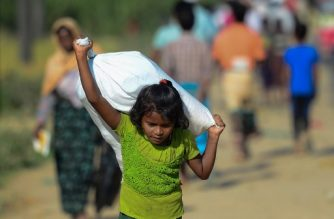 A Rohingya Muslim refugee child carries relief aid through Balukhali refugee camp in the Ukhia district of Bangladesh on November 20, 2017. An estimated 618,000 Muslim Rohingya have fled mainly Buddhist Myanmar since a military crackdown was launched in Rakhine in August triggered an exodus, straining resources in the impoverished country. / AFP PHOTO / Munir UZ ZAMAN