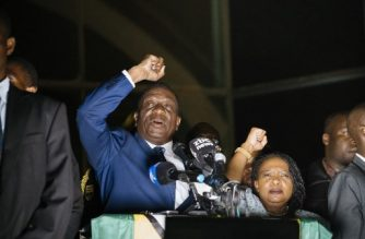 Zimbabwe's incoming president Emmerson Mnangagwa (L) speaks to supporters flanked by his wife Auxilia at Zimbabwe's ruling Zanu-PF party headquarters in Harare on November 22, 2017. Zimbabwe's former vice president Emmerson Mnangagwa flew home on November 22 to take power after the resignation of Robert Mugabe put an end to 37 years of authoritarian rule. Mnangagwa will be sworn in as president at an inauguration ceremony on November 24, officials said.  / AFP PHOTO / MARCO LONGARI