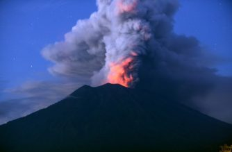 A general view shows Mount Agung erupting seen at night from Kubu sub-district in Karangasem Regency on Indonesia's resort island of Bali on November 28, 2017.  Indonesian authorities extended the closure of the international airport on the resort island of Bali for a second day over fears of a volcanic eruption. / AFP PHOTO / SONNY TUMBELAKA