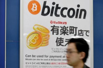 (FILES) This file photo taken on April 7, 2017 shows a man walking past a signboard informing customers that Bitcoin can be used for payment at a store in Tokyo. Bitcoin breaks 10,000 USD barrier for first time on November 29, 2017. / AFP PHOTO / Toru YAMANAKA