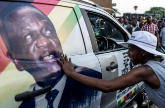 A supporter of Emmerson Dambudzo Mnangagwa touches an image of the politician glued on a SUV at the ZANU-PF headquarter in Harare, on November 22, 2017. Zimbabwe's former vice president Emmerson Mnangagwa flew home on November 22 to take power after the resignation of Robert Mugabe put an end to 37 years of authoritarian rule. Mnangagwa will be sworn in as president at an inauguration ceremony on November 24, officials said. / AFP PHOTO / MARCO LONGARI