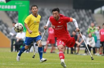 """In this picture taken on November 12, 2017, He Yiyi kicks the ball during a football match with a local team in Guangzhou, Guangdong province. The exploits of 21-year-old He Yiyi, who lost his leg to childhood cancer and uses crutches to support himself when playing, have earned him several endearing nicknames including """"Angel with Broken Wings"""", """"Ball King with One Leg"""" and """"Magic Boy"""". / AFP PHOTO / - / China OUT / To go with Fbl Asia CHN disabled, Focus by Peter Stebbings"""
