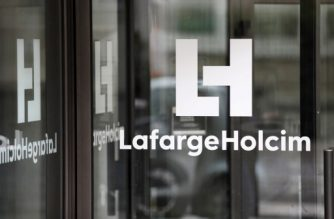 (FILES) This file photo taken on March 9, 2017 in Paris, shows a logo at an entrance of the French headquarters of LafargeHolcim, a group created in 2015 by the merger of French cement manufacturer Lafarge and its Swiss counterpart Holcim. / AFP PHOTO / Thomas Samson