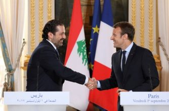 (FILES) This file photo taken on September 1, 2017 shows French President Emmanuel Macron (R) shaking hands with Lebanese Prime Minister Saad Hariri during a press conference at the Murat Lounge in the Elysee Palace in Paris. / AFP PHOTO / ludovic Marin