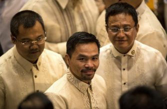 Philippine boxing icon and Senator Manny Pacquiao (C) arrives at the House of Representatives in Manila on July 24, 2017, to attend Philippine President Rodrigo Duterte's second annual state of the nation address. Duterte was to deliver his annual address to parliament days after lawmakers approved his proposal to extend martial law in the south until the end of the year. / AFP PHOTO / NOEL CELIS