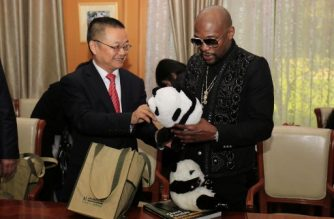 "This picture taken on November 30, 2017 shows US boxer Floyd Mayweather (R) receiving a stuffed panda toy during an adoption ceremony after he adopted a panda baby at the Chengdu Research Base of Giant Panda Breeding in Chengdu in China's southwestern Sichuan province. Floyd Mayweather displayed his softer side as he adopted a baby giant panda in China -- and promptly renamed it ""TMT Floyd Mayweather"". / AFP PHOTO / - / China OUT"