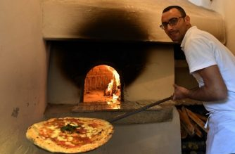 """An Italian """"Pizzaiolo"""" (pizza maker) prepares a Pizza Margherita in the first stone oven where was cooked a Pizza Margherita at the  Capodimonte museum, on December 6, 2017 in Naples. Naples' art of pizza twirling is a candidate to join UNESCO's list of """"intangible heritage"""" and the city is waiting for the decision of the UN cultural body's World Heritage Committee which is reunited in South Korean island of Jeju this week. / AFP PHOTO / TIZIANA FABI"""