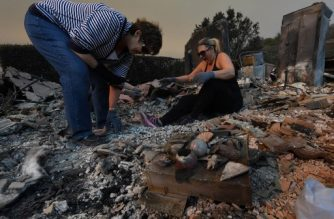 Members of the Reinhardt family sort through the remains of their family home after the Thomas wildfire swept through Ventura, California on December 6, 2017. California motorists commuted past a blazing inferno Wednesday as wind-whipped wildfires raged across the Los Angeles region, with flames  triggering the closure of a major freeway and mandatory evacuations in an area dotted with mansions. / AFP PHOTO / MARK RALSTON