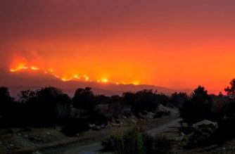 The Thomas Fire burns behind trails on Old Baldwin Road in Ojai, California on December 6, 2017. Local emergency officials warned of powerful winds on December 7 that will feed wildfires raging in Los Angeles, threatening multi-million dollar mansions with blazes that have already forced more than 200,000 people to flee. / AFP PHOTO / Kyle Grillot